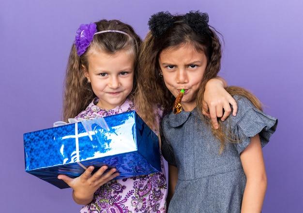 Blij klein blond meisje dat een geschenkdoos vasthoudt en staat met een vrolijk klein brunette meisje dat een feestfluitje blaast geïsoleerd op een paarse muur met kopieerruimte