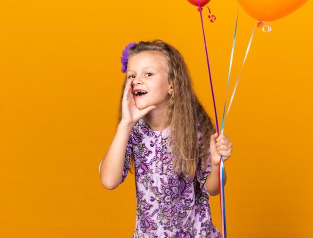 Blij klein blond meisje dat heliumballonnen vasthoudt en de hand dicht bij de mond houdt en iemand belt die op een oranje muur is geïsoleerd met kopieerruimte