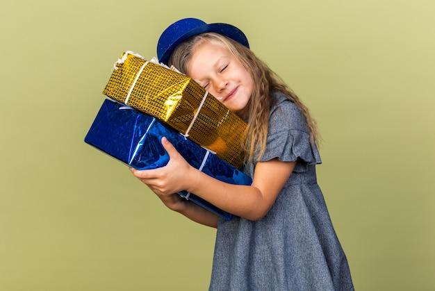 Blij klein blond meisje met blauwe feestmuts houden en zetten hoofd op geschenkdozen geïsoleerd op olijfgroene muur met kopie ruimte