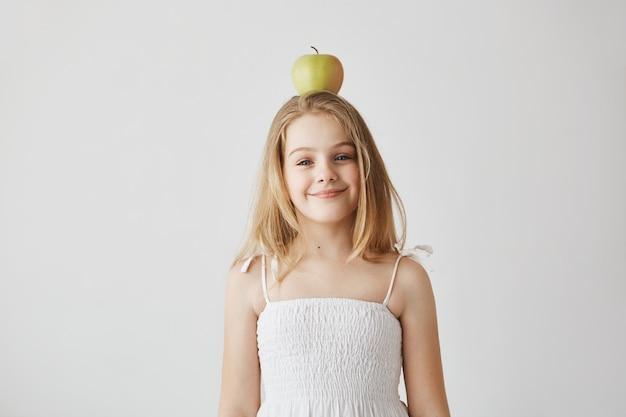 Blij klein blond meisje met blauwe ogen en aangename glimlach in witte jurk grappig poseren met appel op haar hoofd voor familie video-archief. gelukkige momenten van het leven.