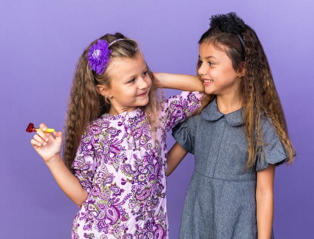 Blij klein blond meisje met feestfluitje en kijkend naar lachend klein brunette meisje geïsoleerd op paarse muur met kopieerruimte