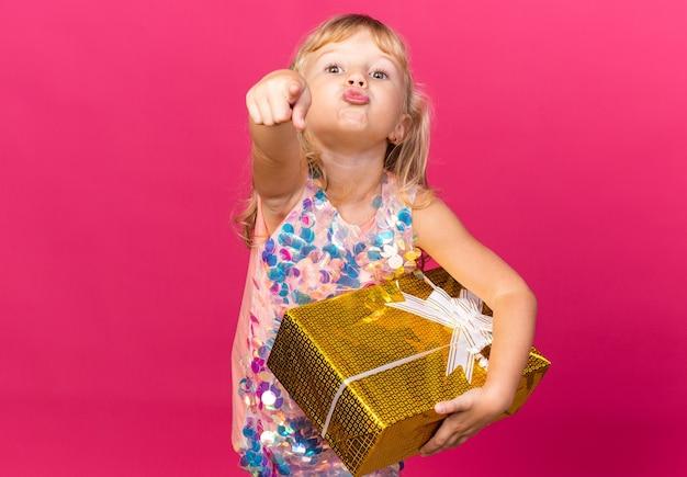 Blij klein blond meisje met geschenkdoos en wijzend geïsoleerd op roze muur met kopieerruimte