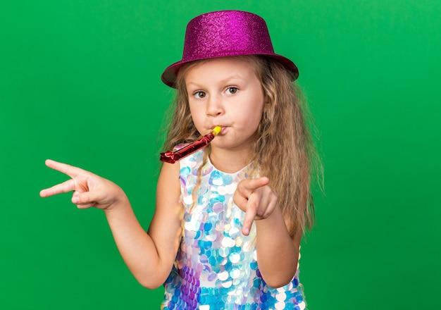 Blij klein blond meisje met paarse feestmuts die feestfluit blaast en wijst naar zijkanten geïsoleerd op groene muur met kopieerruimte