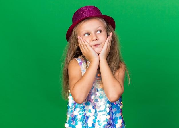 Blij klein blond meisje met paarse feestmuts legt handen op gezicht en kijkt naar kant geïsoleerd op groene muur met kopieerruimte