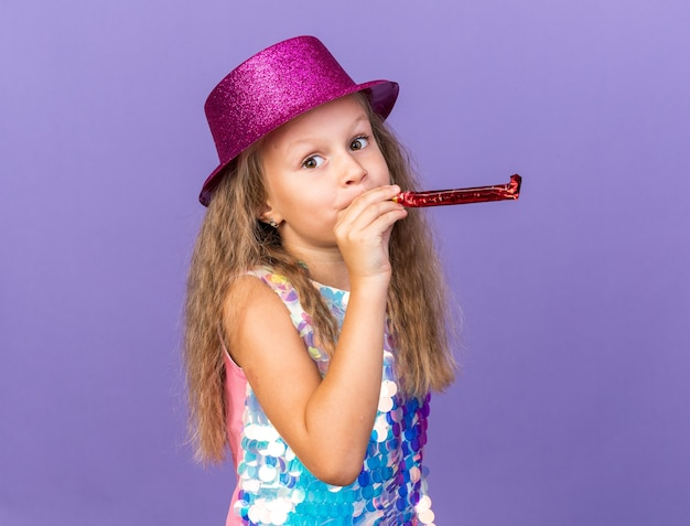 Blij klein blond meisje met violette feestmuts partij fluit blazen en kijken geïsoleerd op paarse muur met kopie ruimte