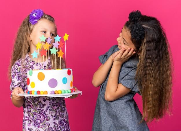 Blij klein kaukasisch meisje dat naar een klein blond meisje kijkt met verjaardagstaart geïsoleerd op een roze muur met kopieerruimte