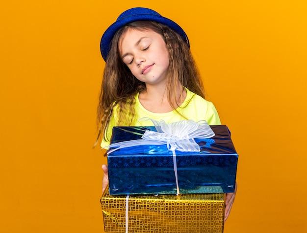 Blij klein kaukasisch meisje met blauwe feestmuts die zich met gesloten ogen bevinden die giftdozen houden die op oranje muur met exemplaarruimte worden geïsoleerd