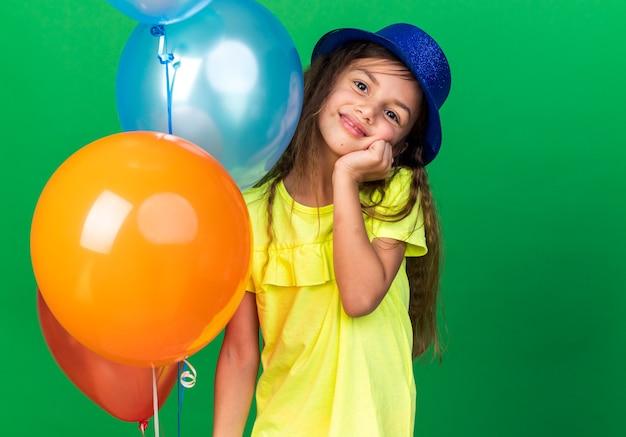 Blij klein kaukasisch meisje met blauwe feestmuts hand op gezicht zetten en helium ballonnen geïsoleerd op groene muur met kopie ruimte te houden