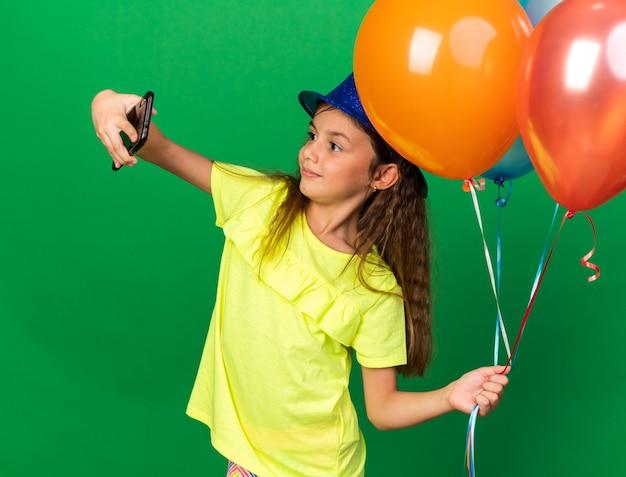 Blij klein kaukasisch meisje met blauwe feestmuts helium ballonnen te houden en selfie te nemen op telefoon geïsoleerd op groene muur met kopie ruimte