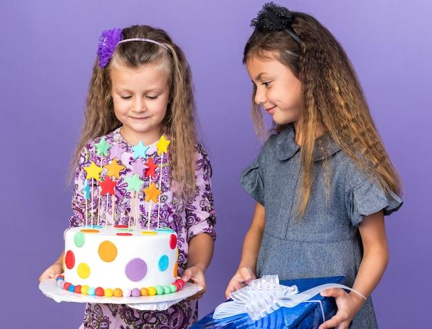 Blij klein kaukasisch meisje met geschenkdoos en kijkend naar blond meisje met verjaardagstaart geïsoleerd op paarse muur met kopieerruimte