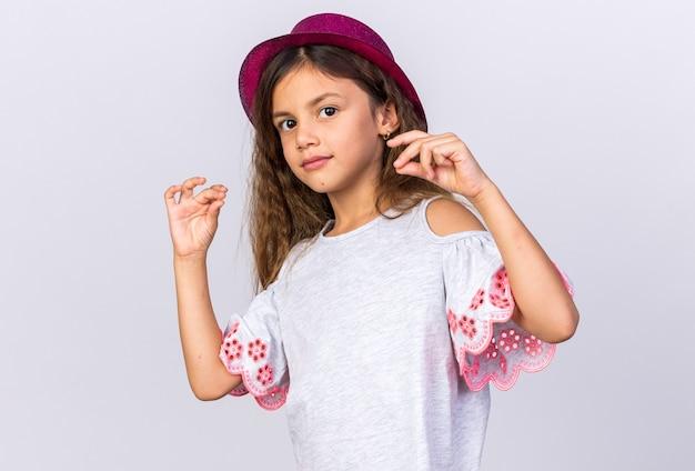 Blij klein kaukasisch meisje met paarse feestmuts die doet alsof ze iets vasthoudt dat op een witte muur met kopie ruimte wordt geïsoleerd