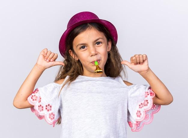 Blij klein kaukasisch meisje met paarse feestmuts die feestfluit blaast en naar zichzelf wijst geïsoleerd op een witte muur met kopieerruimte