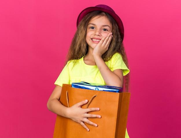 Blij klein kaukasisch meisje met paarse feestmuts hand op gezicht zetten en geschenkdoos houden in papieren zak geïsoleerd op roze muur met kopie ruimte