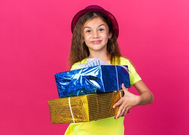 Blij klein kaukasisch meisje met paarse feestmuts met geschenkdozen geïsoleerd op roze muur met kopieerruimte