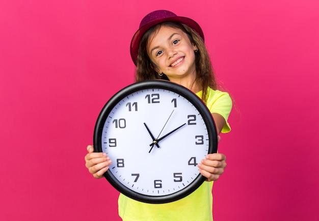 Blij klein kaukasisch meisje met paarse feestmuts met klok geïsoleerd op roze muur met kopie ruimte