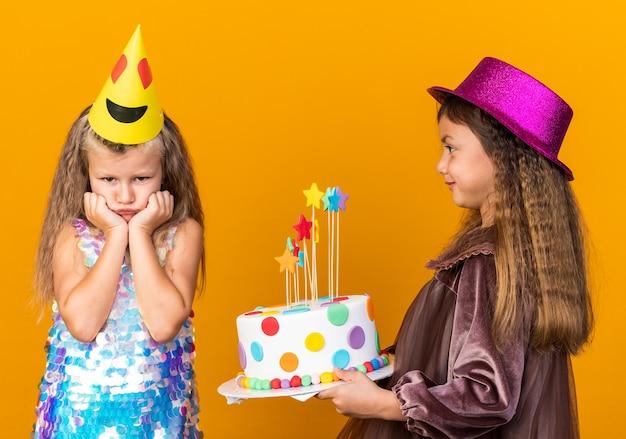 Blij klein kaukasisch meisje met paarse feestmuts met verjaardagstaart en kijken naar verdrietig klein blond meisje met feestmuts geïsoleerd op oranje muur met kopie ruimte