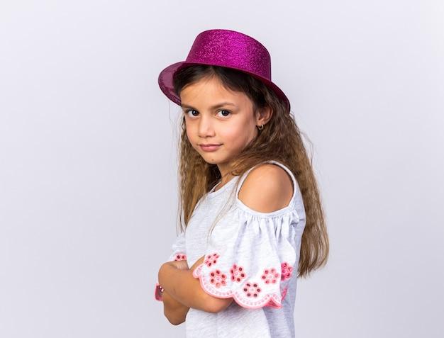 Blij klein kaukasisch meisje met paarse feestmuts zijwaarts staande met gekruiste armen geïsoleerd op een witte muur met kopie ruimte