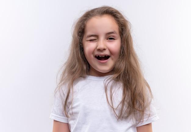 Blij klein schoolmeisje dat een witte t-shirt droeg knipperde op geïsoleerde witte muur