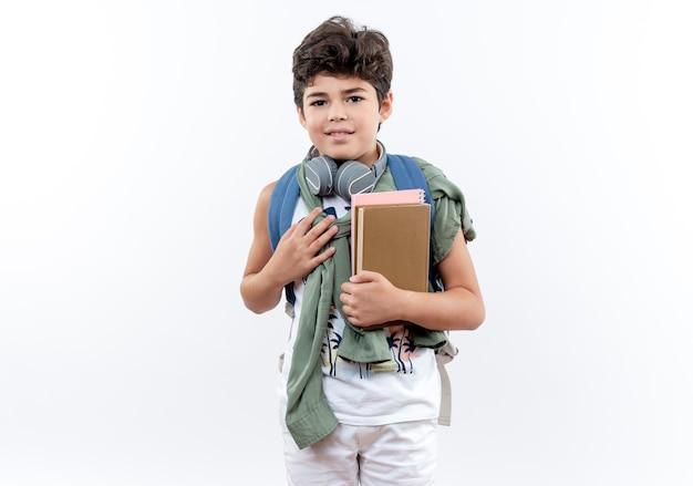 Blij kleine schooljongen met rugzak en koptelefoon met boek