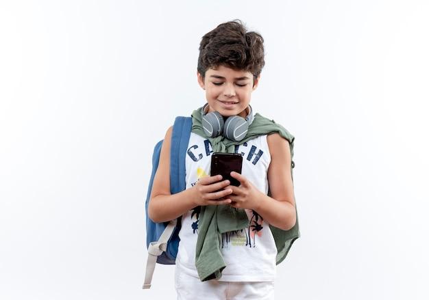 Blij kleine schooljongen met rugzak en koptelefoon nummer kiezen