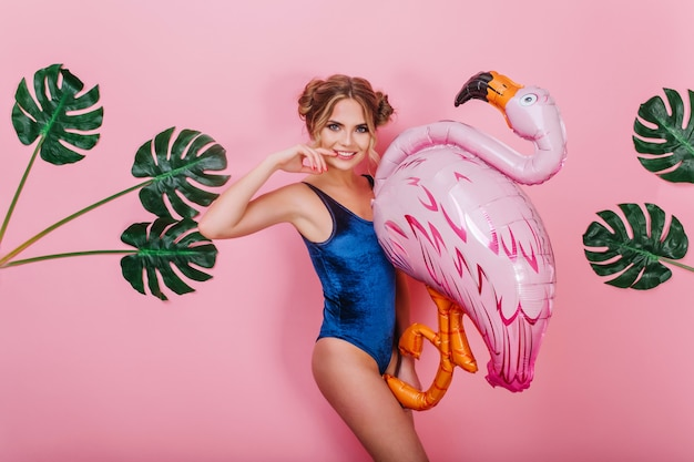 Blij knap meisje met mooi kapsel wat betreft haar gezicht en opblaasbare vogel met planten op de achtergrond te houden. portret van jonge lachende vrouw in vintage romper poseren met speelgoed flamingo