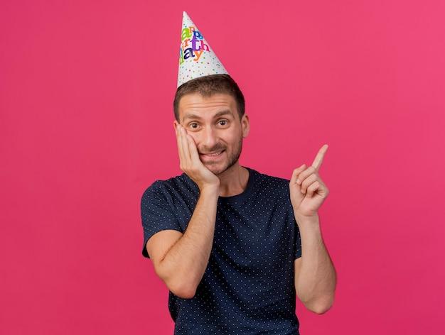 Blij knappe blanke man met verjaardag pet legt hand op gezicht wijzend naar kant geïsoleerd op roze achtergrond met kopie ruimte