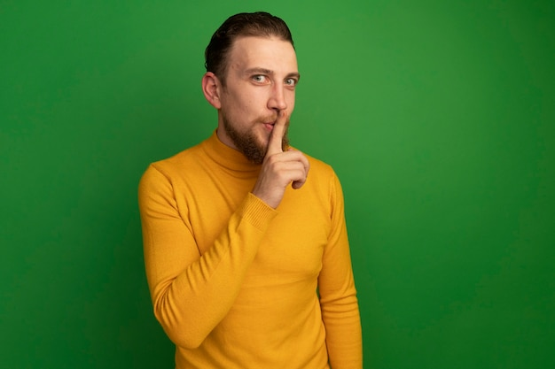 Blij knappe blonde man doet stilte gebaar op groen