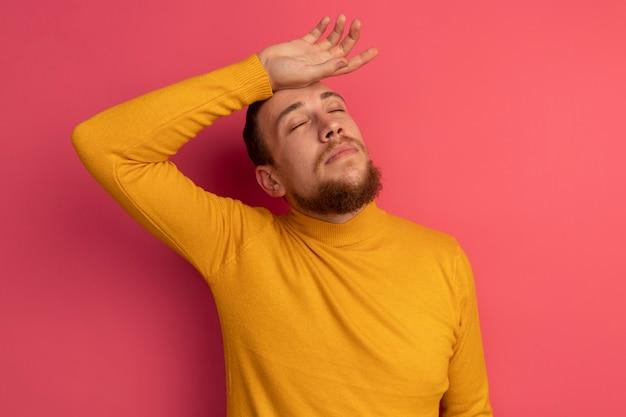 Blij knappe blonde man staat met gesloten ogen hand op het voorhoofd op roze te zetten