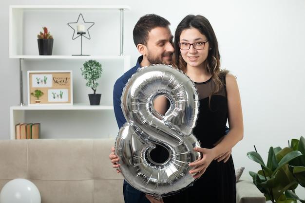Blij knappe man kijken naar mooie jonge vrouw in optische bril met ballon vormige acht staande in de woonkamer op maart internationale vrouwendag