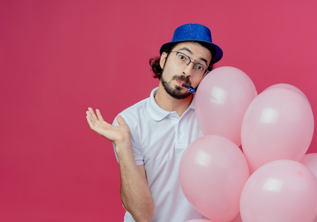 Blij knappe man met bril en blauwe hoed met ballonnen fluitje blazen en verspreid hand geïsoleerd op roze achtergrond met kopie ruimte
