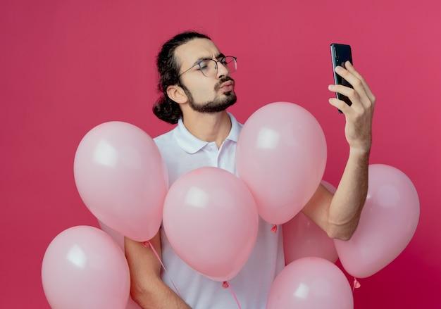 Blij knappe man met bril met ballonnen en neem een selfie geïsoleerd op roze achtergrond