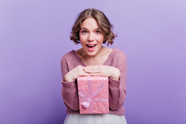 Blij kortharige vrouw poseren met schattige roze doos aanwezig en glimlachen. betoverend krullend meisje dat geniet van fotoshoot met nieuwjaarscadeau op paarse muur.