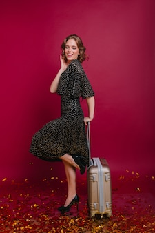 Blij kortharige vrouw staande op een been met koffer en lachend met gesloten ogen