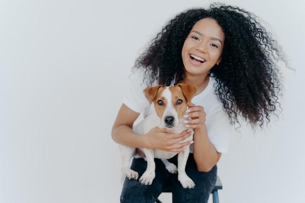 Blij krullend meisje dat haar hond aait, verheugt zich op het kopen van jack russell terrier,