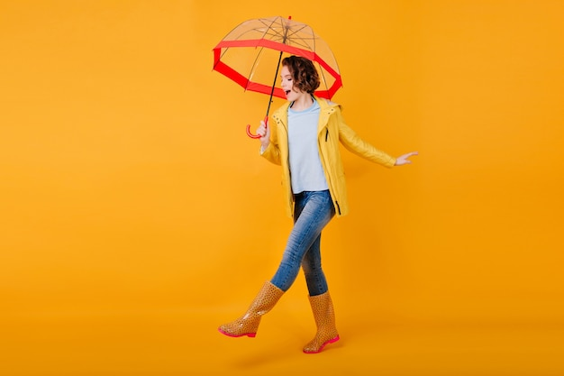 Blij krullend meisje in jeans grappige dansende trendy parasol te houden. studio portret van geïnspireerde jonge vrouw in rubberen schoenen gek rond op felgele muur en glimlachen.