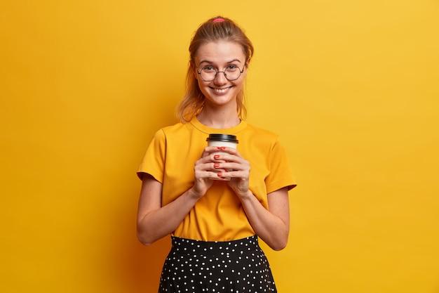 Blij lachend europees meisje heeft een prettige uitstraling drankjes om mee te nemen koffie heeft een vrolijke bui