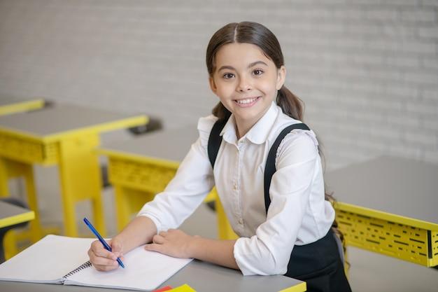 Blij lachend meisje in schooluniform met pen en notitieblok achter haar bureau op school