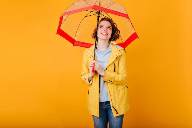 Blij lachend meisje in trendy herfstkledij staande onder parasol. indoor portret van prachtige jonge vrouw genieten van fotoshoot met paraplu.