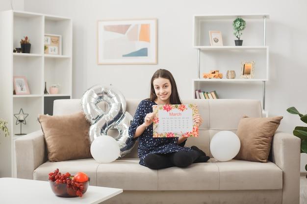 Blij lachend meisje op gelukkige vrouwendag met kalender zittend op de bank in de woonkamer