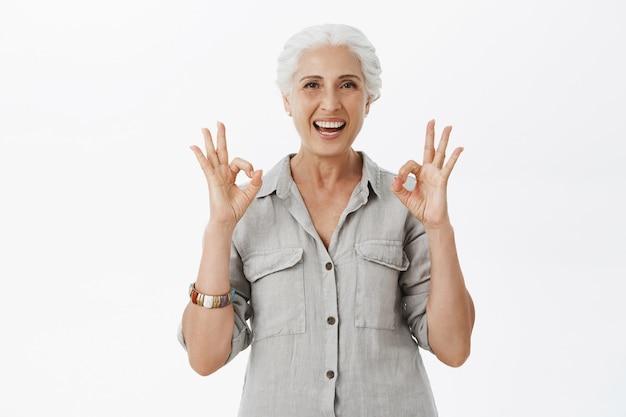 Blij lachende oude dame met goed gebaar ter goedkeuring, bedrijf aanbevelen, zoals idee