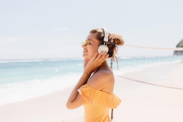 Blij lachende vrouw met gebruinde huid poseren op het strand met charmante glimlach. outdoor portret van enthousiast meisje draagt grote witte koptelefoon tijdens het koelen aan de kust van de oceaan.
