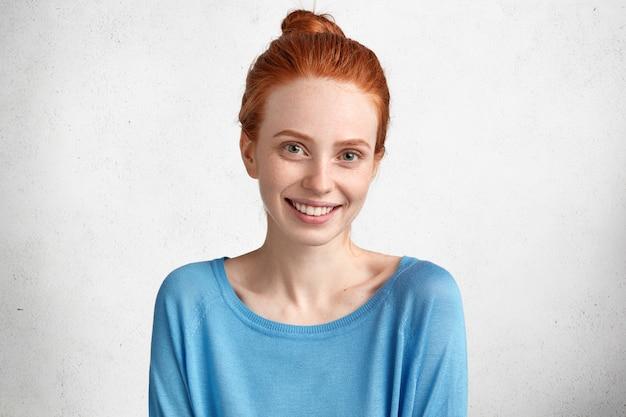 Blij lachende vrouw met sproeten huid en positieve glimlach, gekleed in blauwe casual trui, in hoge geest na date met vriendje, geïsoleerd over wit