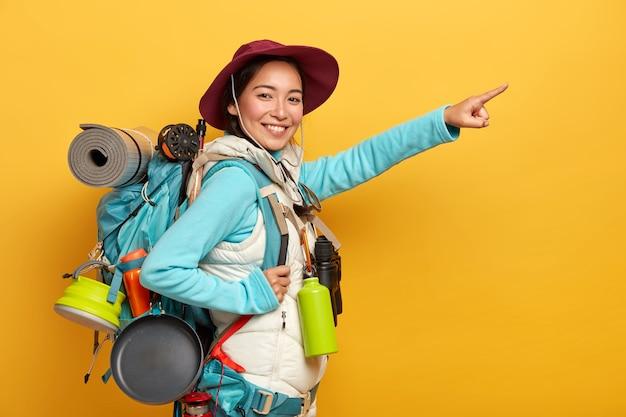 Blij lachende wandelaar nonchalant gekleed, staat met rugzak tegen gele achtergrond
