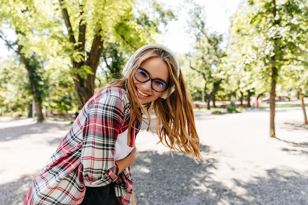 Blij langharig meisje dat van muziek in park geniet. glamoureuze blonde dame in koptelefoon dansen in zonnige dag.