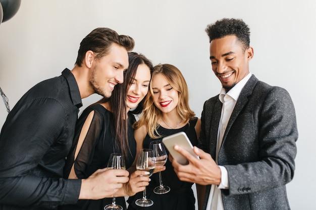 Blij man in vintage tweed jasje selfie maken met vrienden op verjaardagsfeestje