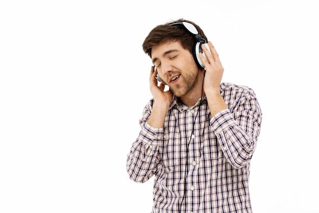 Blij man muziek luisteren in de koptelefoon, glimlach