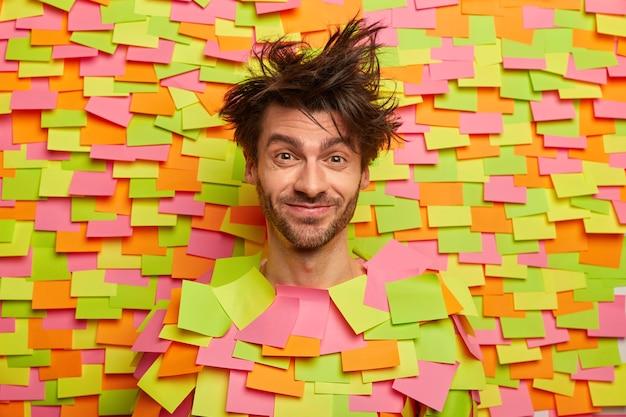 Blij mannelijk gezicht door gat in papieren muur met gekleurde stickers, heeft rommelig haar, stoppels, blij om iets leuks te horen, in goed humeur, dwazen rond. menselijke emoties en gevoelens concept