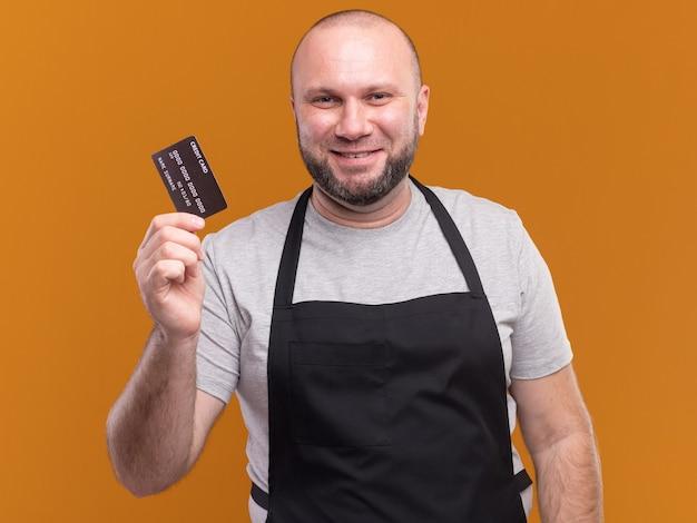 Blij mannelijke kapper van middelbare leeftijd in uniform met creditcard geïsoleerd op oranje muur