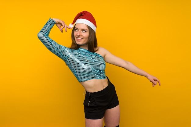 Blij meisje dansen in een kerstmuts op een gele achtergrond