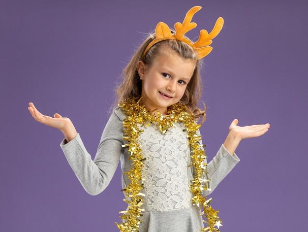 Blij meisje dat de hoepel van het kerstmishaar met slinger op hals spreidt die handen op blauwe achtergrond wordt geïsoleerd